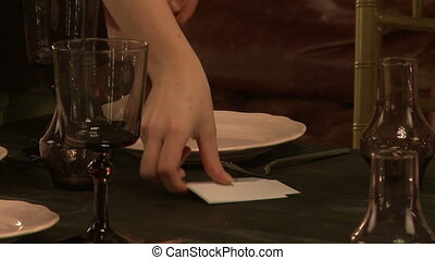 Restaurant worker lays out name cards in plate, close-up