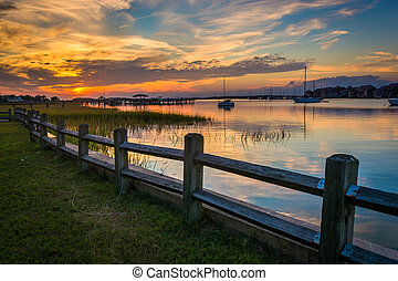 Fence and sunset over the Folly River, in Folly Beach, South...