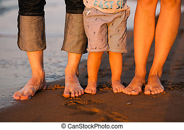 feet of a young family on a sea beach