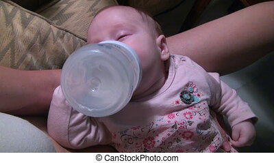baby drinking herself bottle
