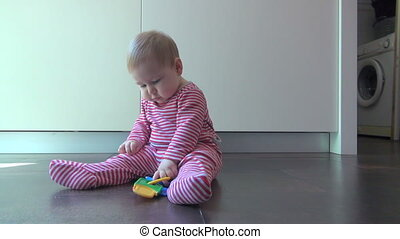 baby playing with plastic keys - nine month old baby lying...