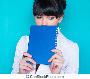 Young beautiful woman holding a address book