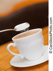 pour sugar to milk coffee of classical white cup on table...