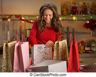 Smiling young woman with shopping bags in christmas...