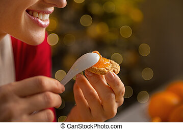 Closeup on happy young woman putting orange jam on cookie