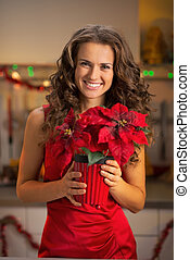 Portrait of happy young woman holding christmas rose