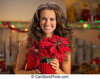 Portrait of happy young woman with christmas rose
