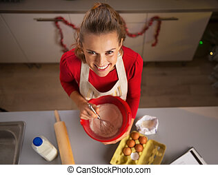 Happy young housewife whisking dough