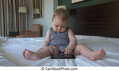 baby with smartphone in bed - baby nine month old playing...