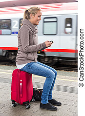 woman waiting for train and writes sms - a young woman...