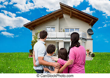 Family Looking At New House On Grassy Field