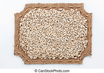 Figured frame of burlap with sunflower seeds, on a white...