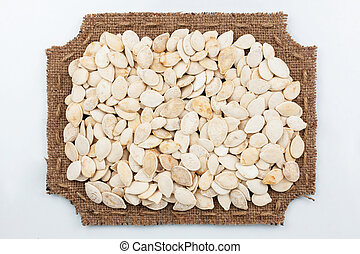 Figured frame of burlap with pumpkin seeds, on a white...