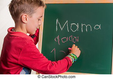 school child with school board - a child writes the word mom...