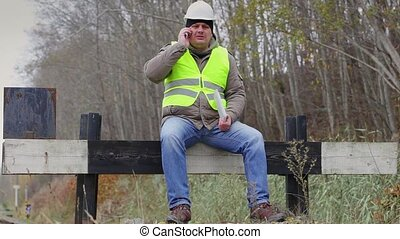Worker with tablet PC and cell phone on the defence barrier