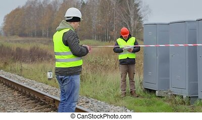 Worker with warning tape on railway