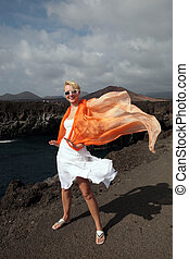 attractive woman with white dress on volcanic lava rocks