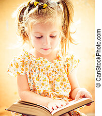 little girl reading the book - sweet happy little girl...