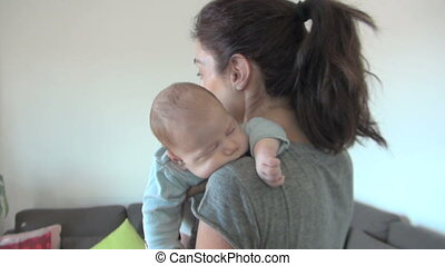mother cradling baby two month old in her shoulder dancing...
