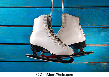 ice skates on blue wooden background - pair of white ice...