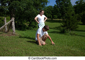 Yard Work - A teenager doing yard work with a woman
