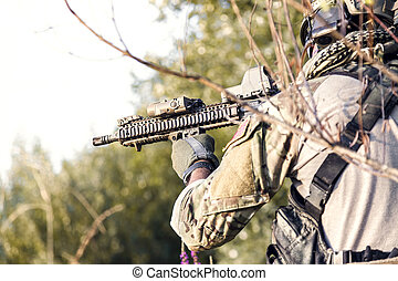 Close up of American Soldier aiming his rifle on the bushes