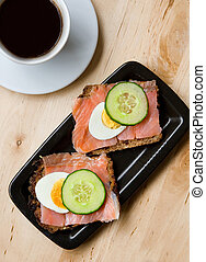 Tasty sandwiches with rye bread, smoked salmon, egg and...