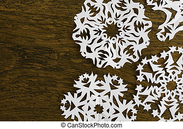 White paper christmas snowflake on a wood background