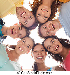 group of smiling teenagers - friendship, youth and people -...
