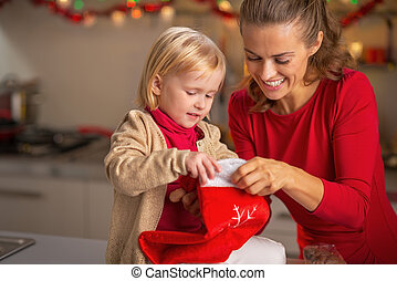 Portrait of happy mother and baby with christmas stocking in...