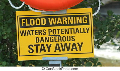 Flood warning - Flood warning sign with river in background...