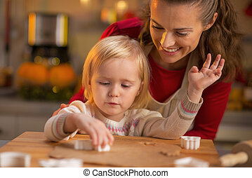 Happy mother and baby making christmas cookies