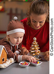 Happy mother and baby making cookie christmas tree