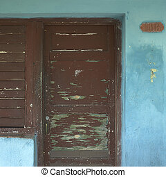 Old brown door on a blue house