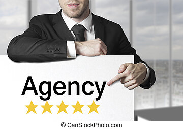 businessman pointing on sign agency - businessman in black...