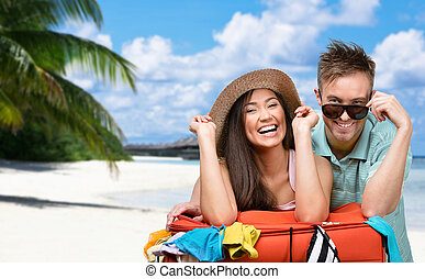Happy couple packs up suitcase with clothing for traveling -...
