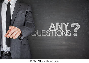 Any Questions concept on black Blackboard with businessman
