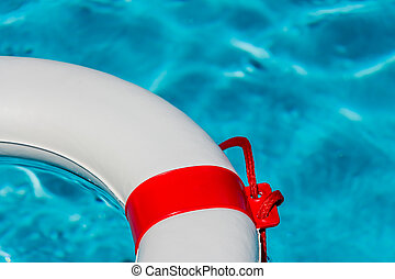lifebuoy in a swimming pool - an emergency tire floating in...