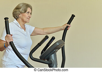 Portrait of elderly woman exercising in gym