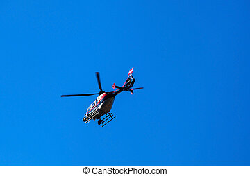 helicopter on blue sky, symbol photo for surveillance and...