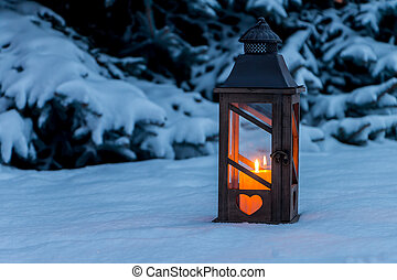 lantern in the snow at christmas - a street lamp glowing in...