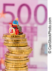 woman in wheelchair on money stack symbol photo for...