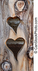 Two hearts cut in wood - Two hearts were cut one above the...