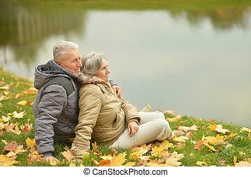 Mature couple sitting near lake