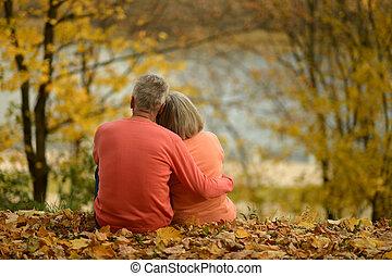 Mature couple sitting near lake back view