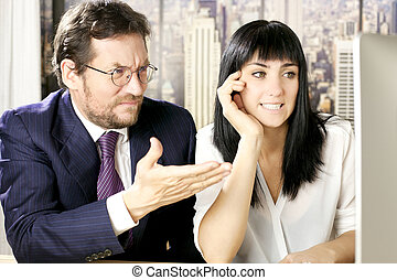 Business man and woman worried in office in front of computer