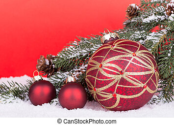 Christmas Balls with evergreen tree branch on snow with red...