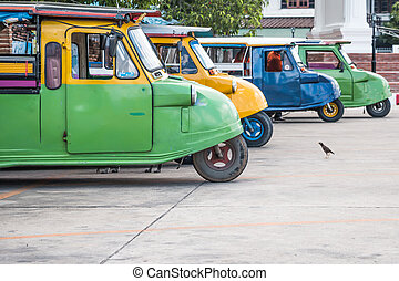 Tuk tuks lined up in a side ally in Bangkok