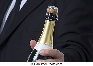Man in siut with Champagne bottle - A man in a suit holding...