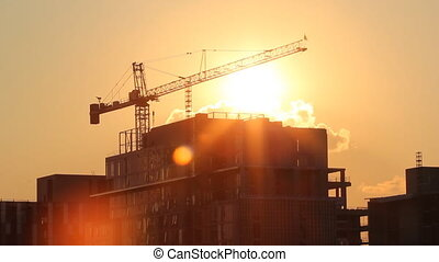 Sunset crane. Timelapse. - Tower crane and condominium at...